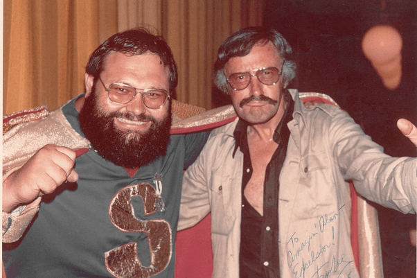 Stan Lee with glasses and a mustache posing with a Marvel fan in the 1970s.