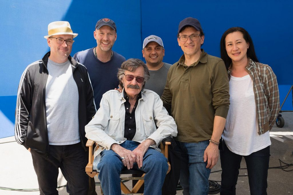 Stan Lee in his 1970s-style costume during the filming of Avengers: Endgame surrounded by the film's directors and other creatives
