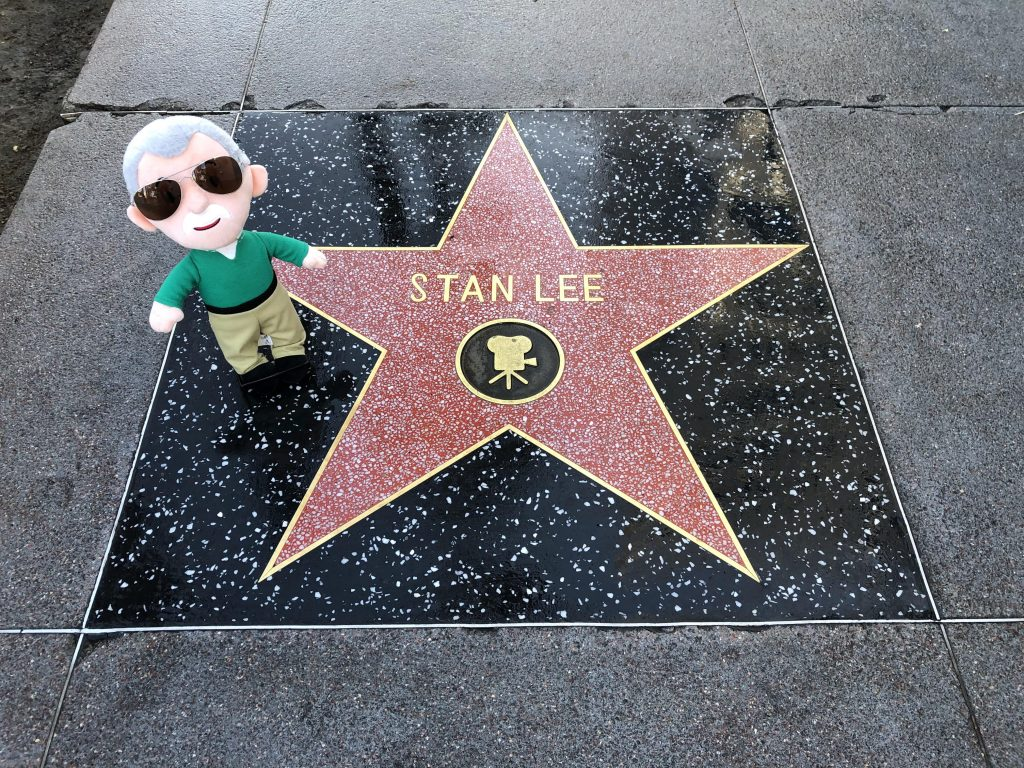 Stan Lees star on the Hollywood Walk of Fame along with a small plush doll of Stan Lee in a green sweater and khaki pants.