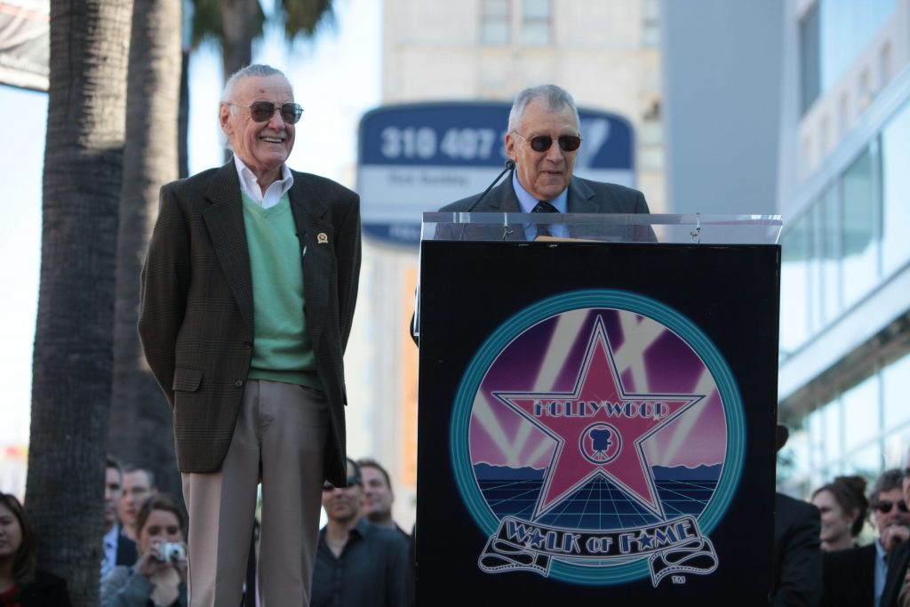 Stan Lee laughing while Gill Champion, standing behind a podium, gives a speech.