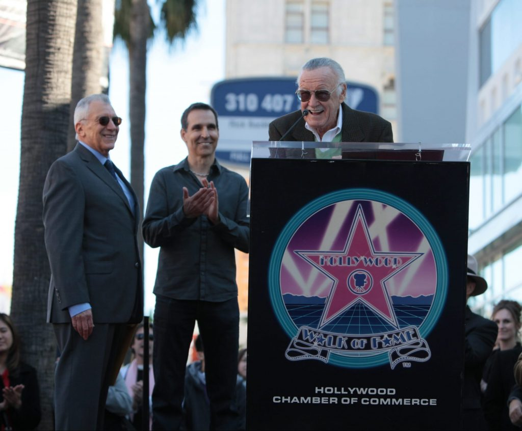 Stan Lee speaking at a podium at this Walk of Fame ceremony with Gill Champion and Todd McFarlane behind him.