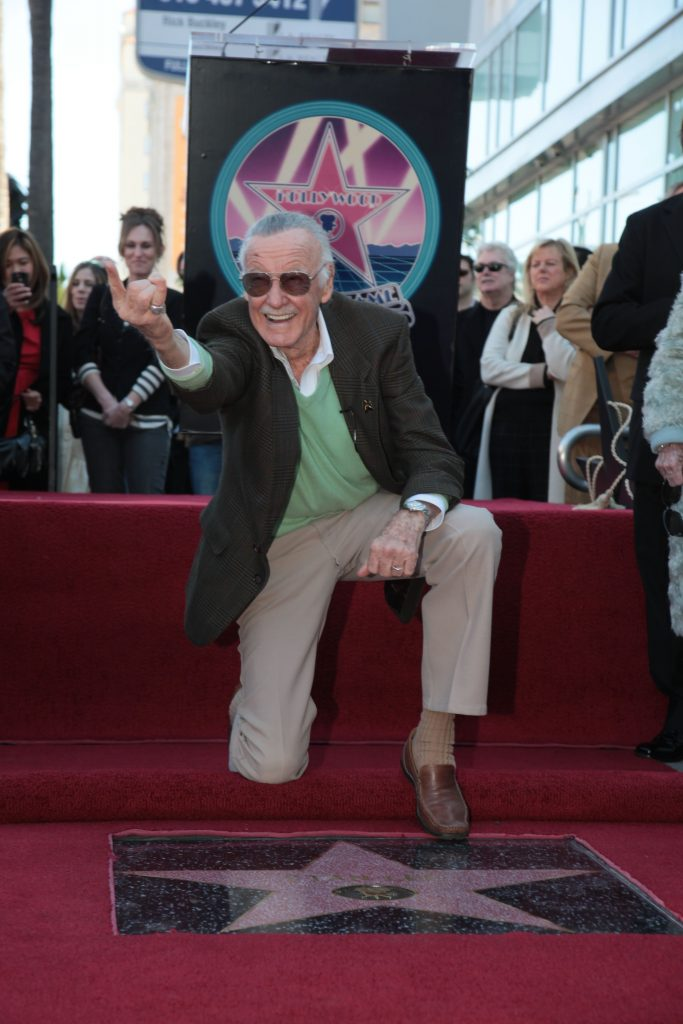 Stan Lee kneeling in front of his star on the Hollywood Walk of Fame.