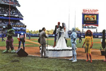 Stan Lee officiating Spider-Man and Mary Jane's wedding on the field of Shea Stadium surrounded by people dressed as Hulk, Captain America, Iceman and Firestar