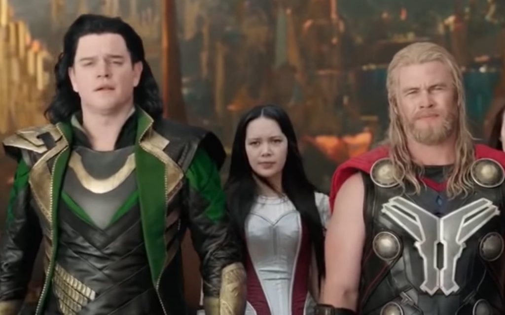 Matt Damon in green and gold attire and Luke Hemsworth in black and gold armor playing stage versions of Loki and Thor in Thor: Ragnarok