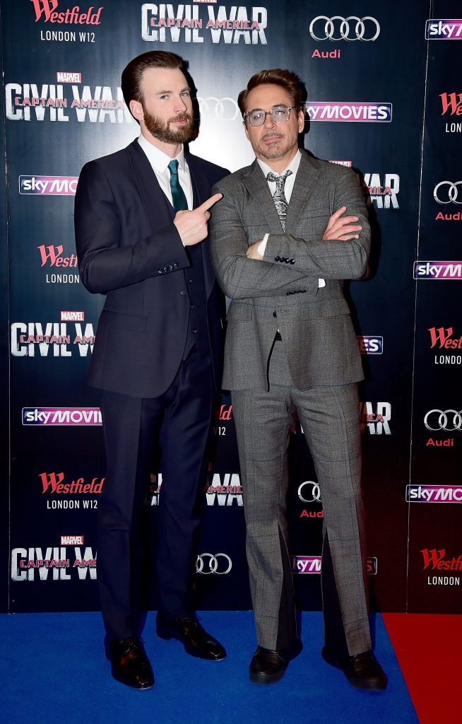 Chris Evans and Robert Downey Jr. on a blue and red carpet for a movie premiere in Europe