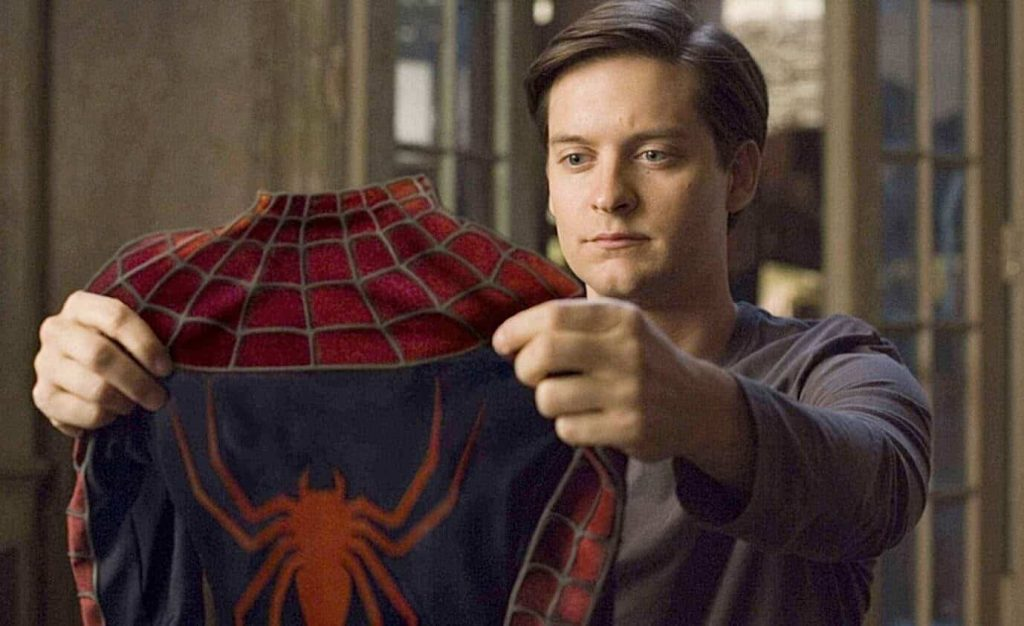 Tobey Maguire holds up a red and blue Spider-Man costume
