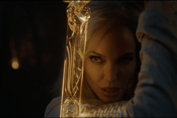A close up of Angelina Jolie in Marvel's The Eternals, holding a gold sword in front of her face