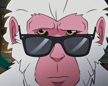 A monkey with white hair and dark sunglasses poses in the middle of the frame with a green ghostly image of a man in the background to the left